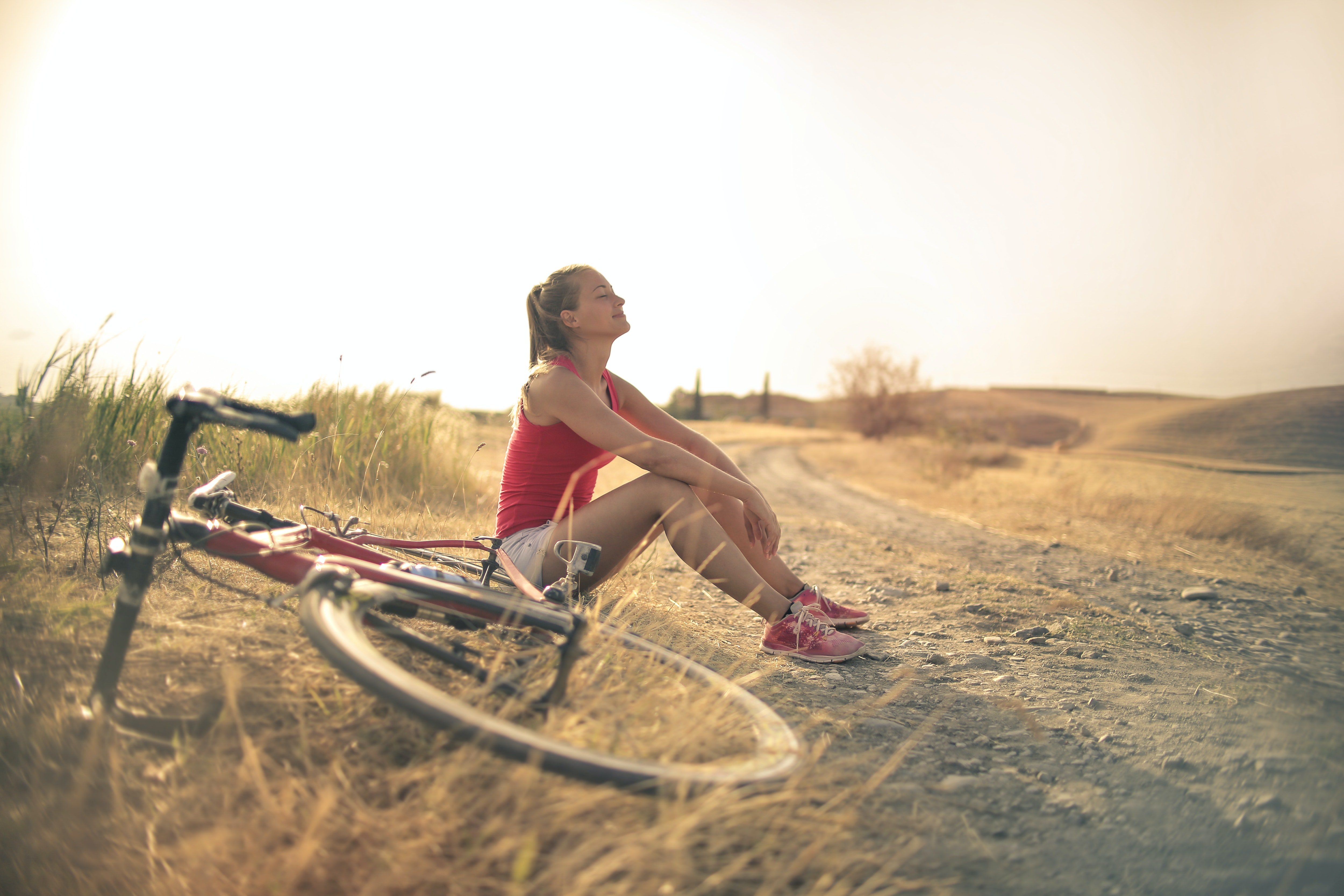 sportive-woman-with-bicycle-resting-on-countryside-road-in-3771836